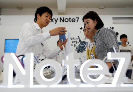 An employee helps customers purchase a Samsung Electronics' Galaxy Note 7 new smartphone at its store in Seoul, South Korea, September 2, 2016. REUTERS/Kim Hong-Ji